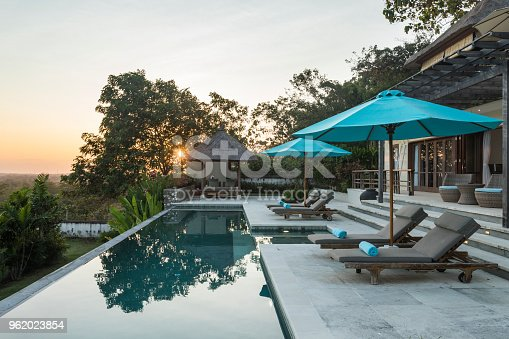 Early morning sunrise at a luxurious villa with a magnificent swimming pool and lounge chairs with the sunbeam slowly breaking through the trees. The villa is situated in Uluwatu in Bali