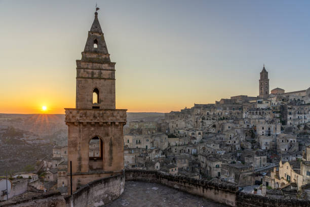 Sunrise in Matera A view of the ancient architecture of Matera with cave dwellings, towers and stone houses during sunrise matera italy stock pictures, royalty-free photos & images