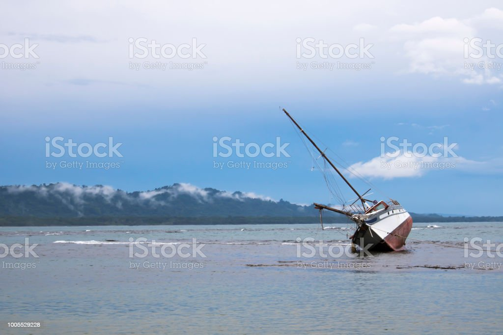 Sunrise in pink and blue over ocean with one tilted boat in foreground stock photo