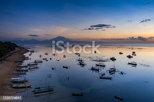 Aerial view of the beach of Sanur in Bali with numerous traditional boats anchored along the beach.