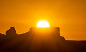 Orange sunrise with the sun rising from behind a butte near Page, Arizona. United States