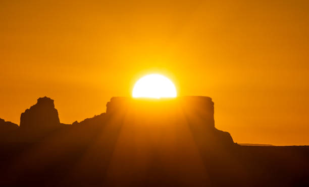 sunrise in the far west mountains Orange sunrise with the sun rising from behind a butte near Page, Arizona. United States page arizona stock pictures, royalty-free photos & images