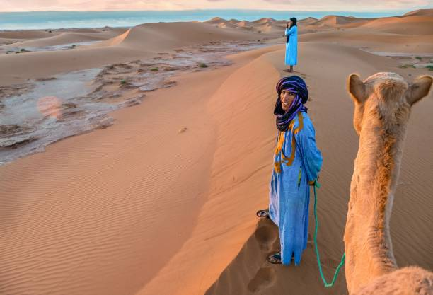 sunrise in the sahara desert, as two nomadic tribesmen wearing traditional blue robes, stand on a sand dune with a camel. - north africa stock photos and pictures