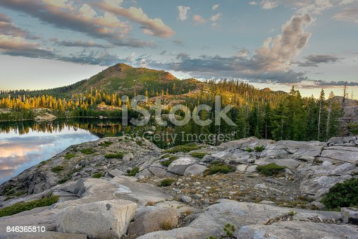 Sunrise over the mountains surrounding Island Lake, South Lake Tahoe, California, USA, featuring dramatic clouds, their reflection in the lake, and an unoccupied tent site on rugged, rocky terrain