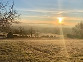 Sunrise on a crisp winter morning in the French countryside, hoarfrost, sunbeams coming through the mist, horizontal view taken from hill, poetic nature background
