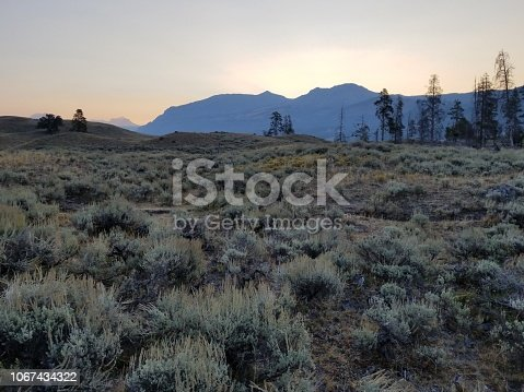 The sun rises over the mountains and the sagebrush valley in Yellowstone National Park.