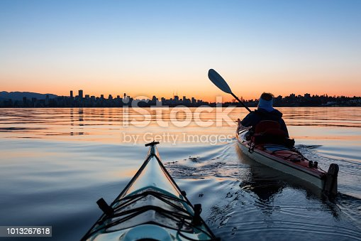 Adventurous Girl Sea Kayaking during a vibrant winter sunrise with City Skyline in Background. Taken in Downtown Vancouver, British Columbia, Canada.