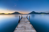 A view looking down a wharf on Lake Atitlán at sunrise.