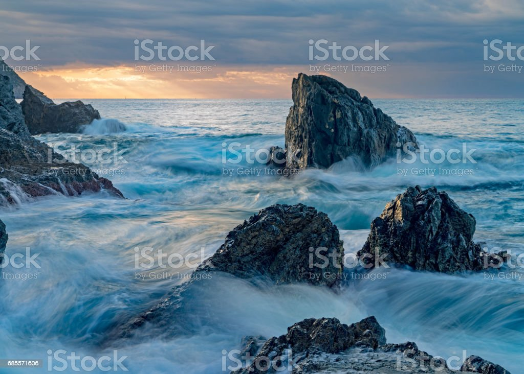 Sunrise landscape of ocean with waves clouds and rocks on beach royalty-free 스톡 사진