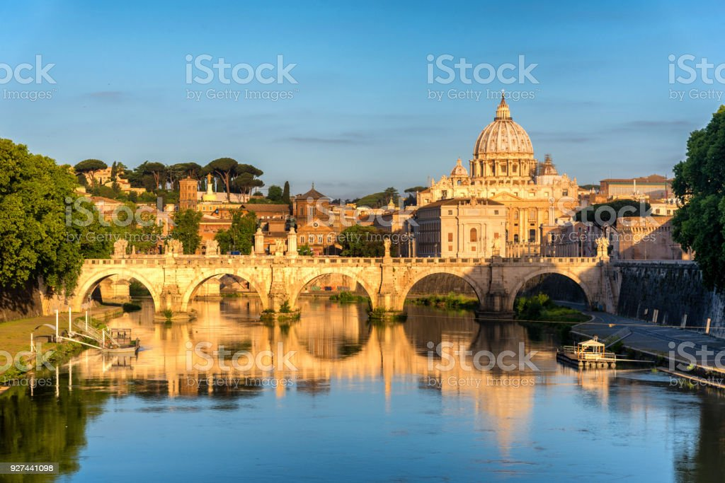 Sunrise landscape view in early morning of St. Peters Basilica in the Vatican and the Ponte Sant'Angelo, Bridge of Angels, at the Castel Sant'Angelo and river Tiber in Rome, Italy stock photo