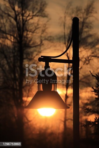 The sun rises into the globe of a lamppost in Alaska on a beautiful winter morning.