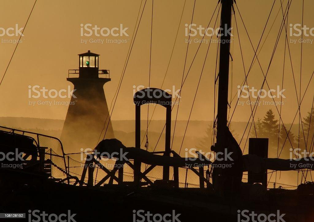Sunrise Lighthouse through Sailboat royalty-free stock photo