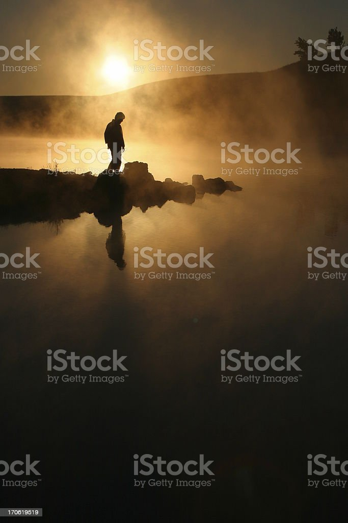 Sunrise morning fog and silhouetted hiker on calm lake royalty-free stock photo