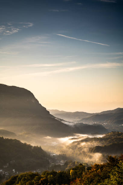 Sunrise morning mist in small village on the Italian Alps, Piedmont, Monte Fenera stock photo