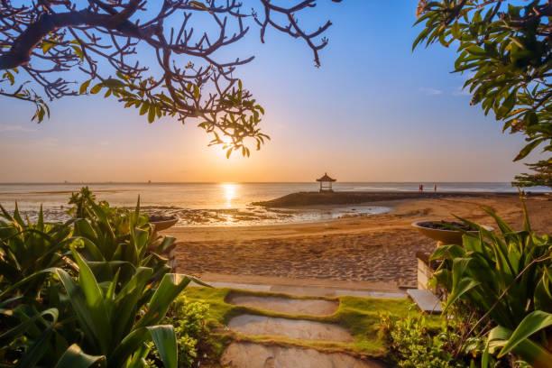 zonsopgang op een strand in bali indonesië - bali stockfoto's en -beelden