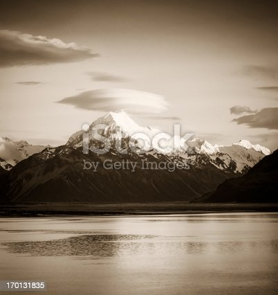 Toned monochrome image of early morning sunlight illuminating the snow and ice on the peak of Mt Cook (Aoraki), topped by a lenticular cloud, on New Zealand's South Island.
