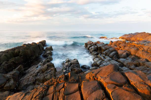 Sunrise on coast of sea stock photo