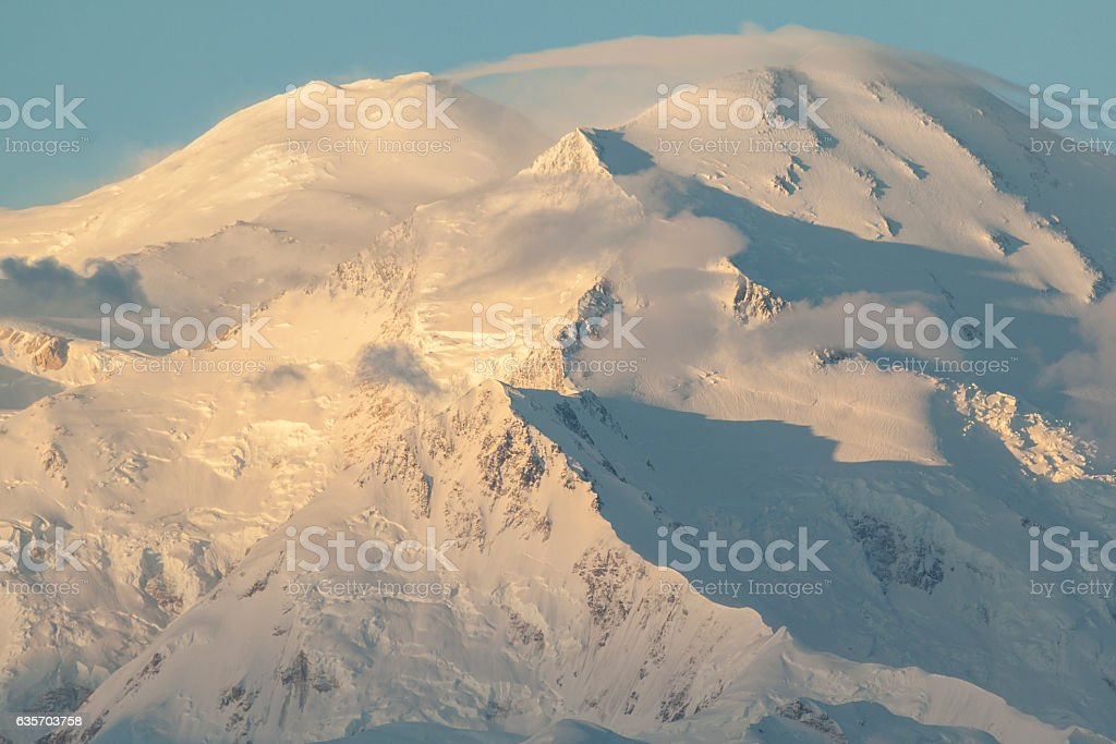Sunrise on Denali as high winds form a lenticular cloud. royalty-free stock photo