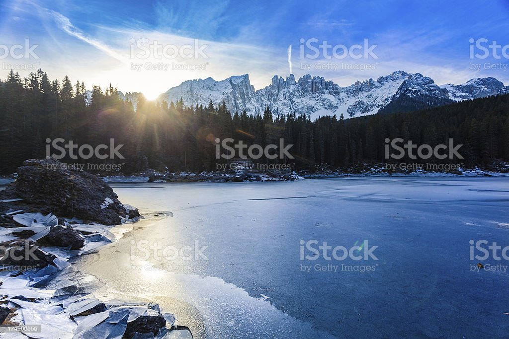 Sunrise on Frozen Mountain Lake of Carezza, Dolomites, Italy stock photo