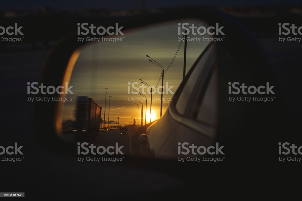 Sunrise on highway road in left side view mirror driver. Focus on reflection in smaller mirror. royalty-free stock photo