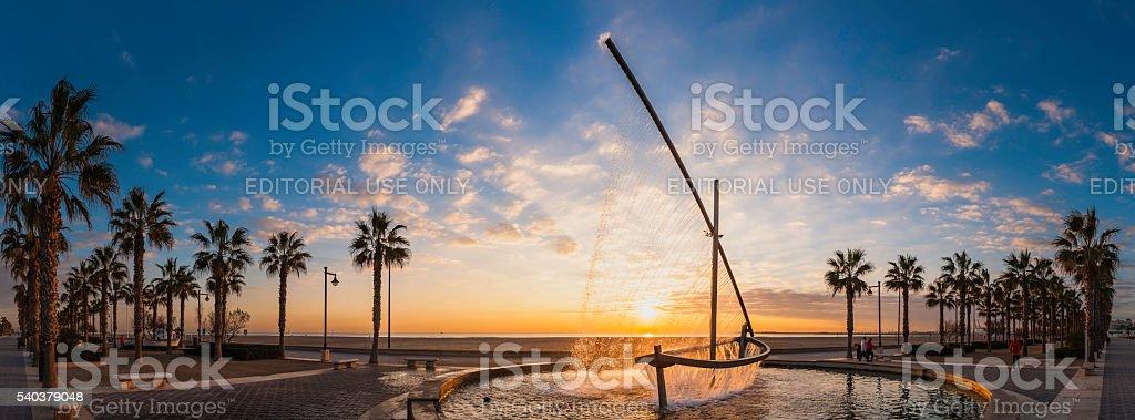 Sunrise on Mediterranean Ocean beach promenade palm trees Valencia Spain stock photo