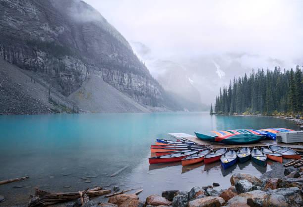 Sunrise on Moraine Lake and colorful canoes stock photo