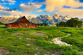 Sunrise light on the vintage Moulton Barn in Mormon row in Jackson Hole, Wyoming.  The Grand Tetons are in the background