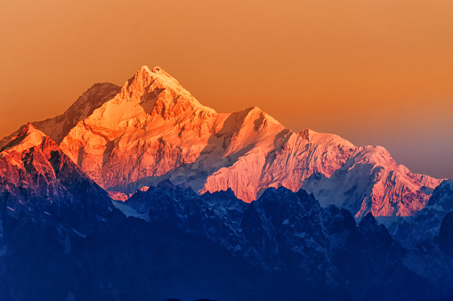 Beautiful first light from sunrise on Mount Kanchenjugha, Himalayan mountain range, Sikkim, India. Orange tint on the mountains at dawn