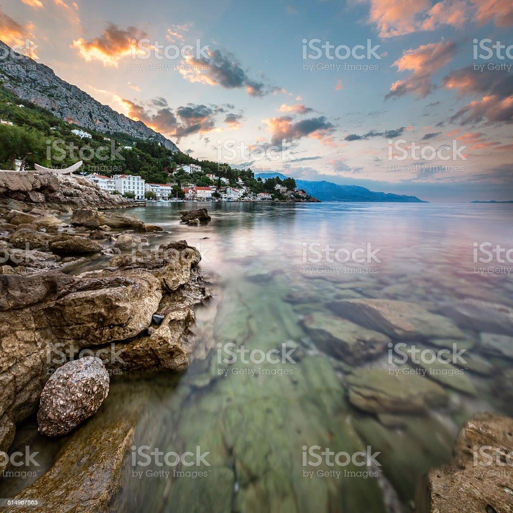 Sunrise on Rocky Beach and Small Village near Omis, Dalmatia stock photo