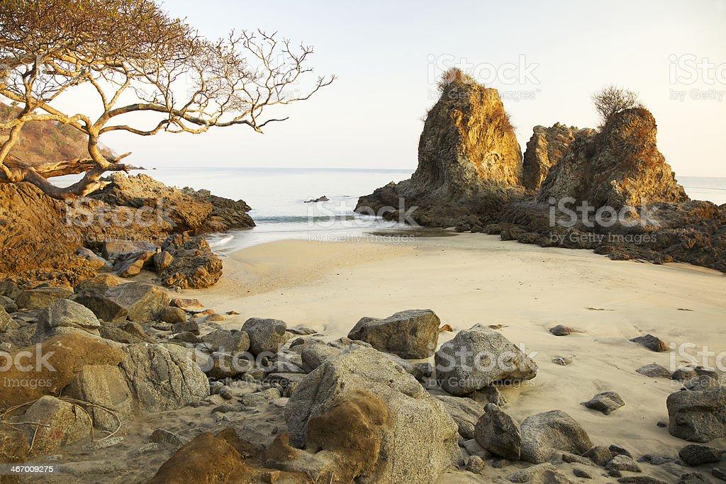 Sunrise on rocky ocean shoreline. stock photo