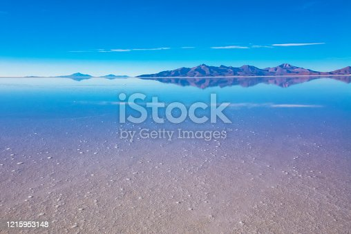 istock Sunrise on Salar de Uyuni in Bolivia covered with water, salt flat desert and sky reflections 1215953148