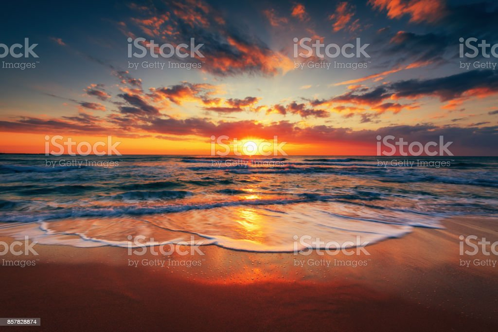 Sunrise on the beach and beautiful cloudscape over the sea stock photo