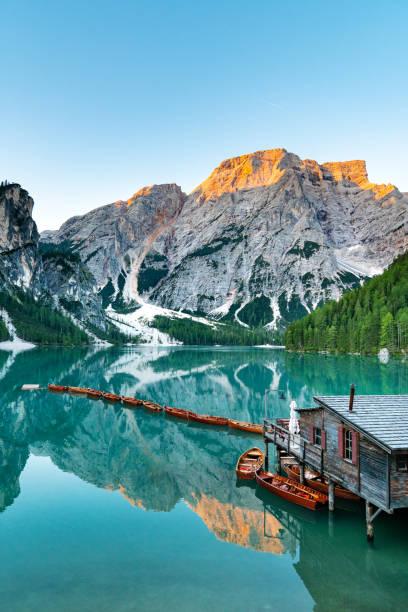 Sunrise on The Pragser Wildsee (Lake Prags, Lake Braies, Lago di Braies) Wooden boats on lake. Silent morning in mountain lake