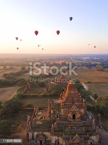 The ancient city of Bagan with over 2000 temples and hot-air balloons flying towards the sunrise