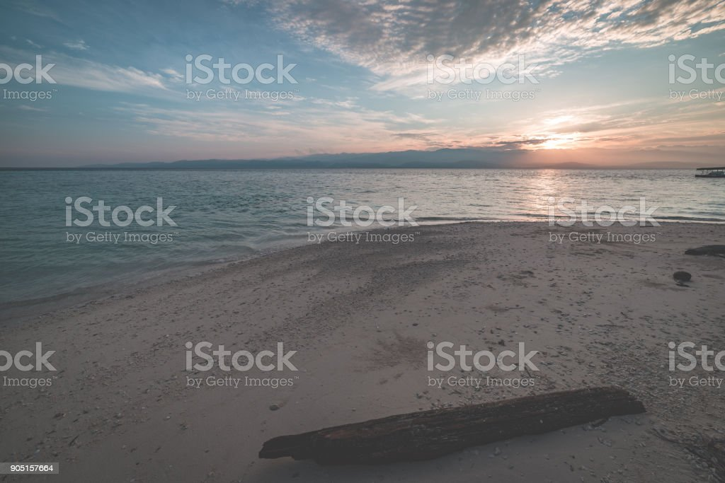 Sunrise on tropical beach, wide angle view in backlight from the coral sandy beach with tree trunk, toned image. stock photo