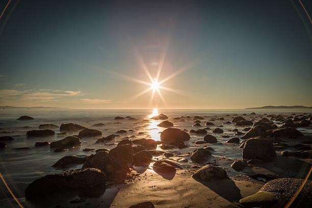 sonnenaufgang oder sonnenuntergang über beach rocks - sternmoos stock-fotos und bilder