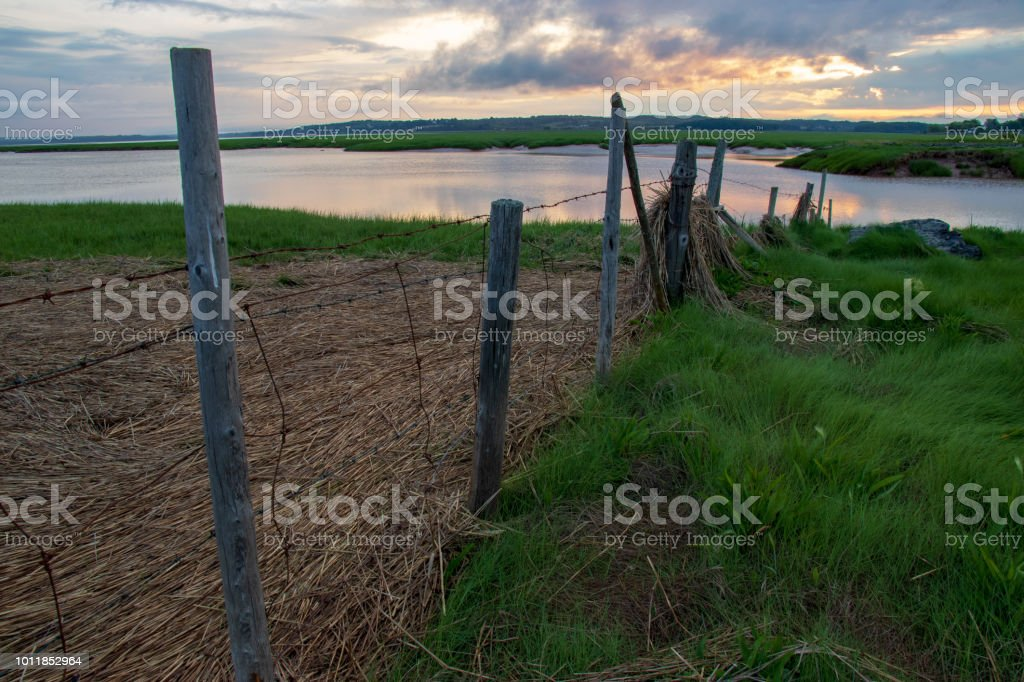 Sunrise over a fence leading down to the tidal Avon River. stock photo