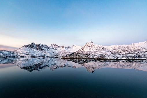 Sunrise over a Fjord in the Lofoten during a cold winter morning at Austvågøy island.
