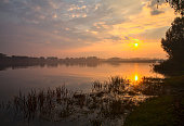 istock Sunrise over a lake with mist in autumn framed by a tree 1282588079