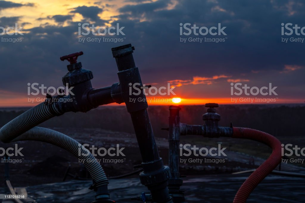 Sunrise over a Landfill showing a methane collection pipeline stock photo