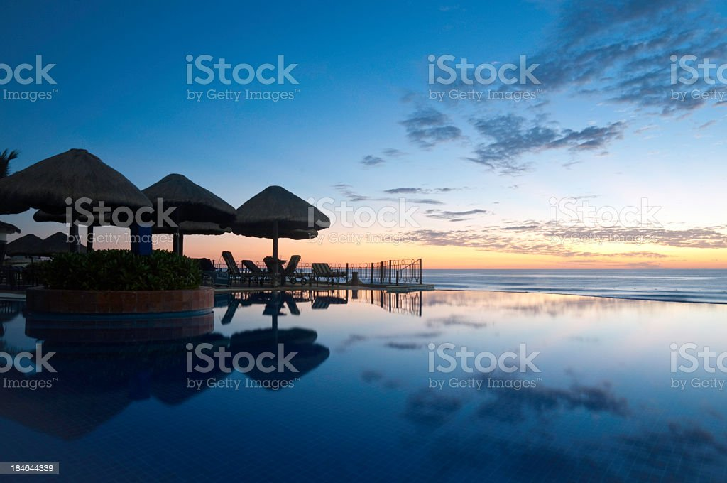 Sunrise over a pool overlooking the ocean stock photo