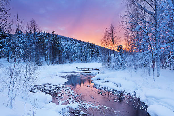Sunrise over a river in winter near Levi, Finnish Lapland stock photo