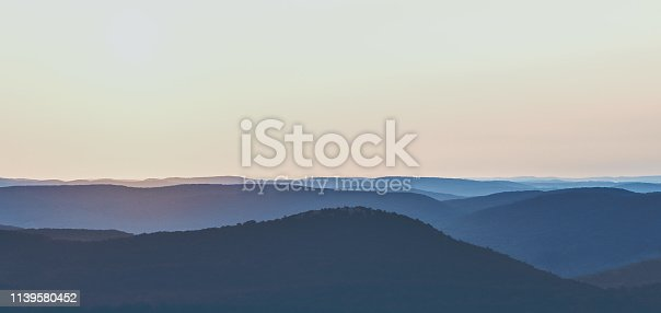 An early morning photo of a silhouetted Hudson Valley New York Mountain Range located in Harriman State Park.