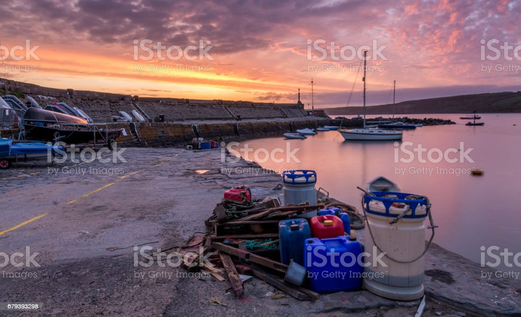 Sunrise, over a stone harbour wall, with commercial fishing items in the foreground royalty-free stock photo