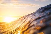 A high key sunrise shining on a forming wave