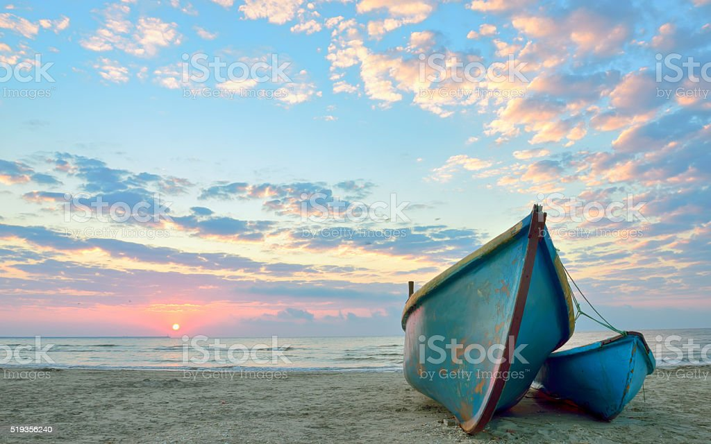 sunrise over an  wooden fishing boats stock photo