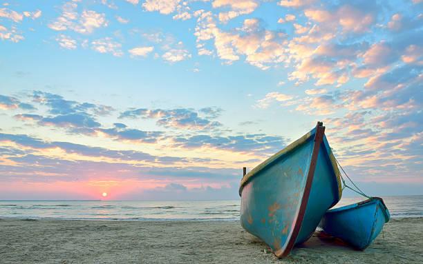sunrise over an  wooden fishing boats - vattenlandskap bildbanksfoton och bilder