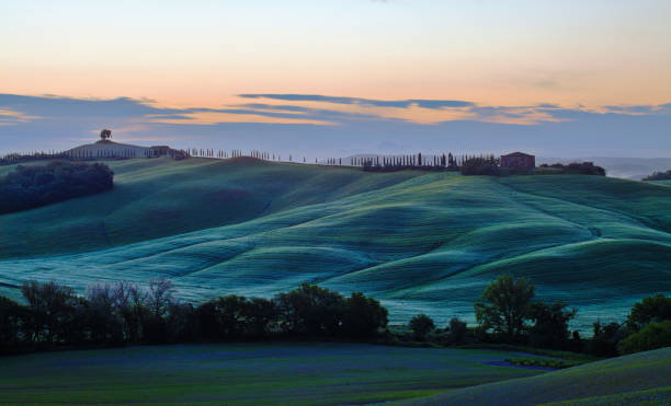 Sunrise over blue curvy hills in Tuscany stock photo