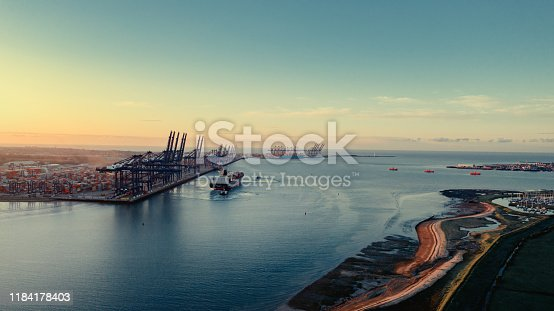 istock Sunrise over Felixstowe Container Port as two tugs shepherd a container ship away from the harbour wall 1184178403