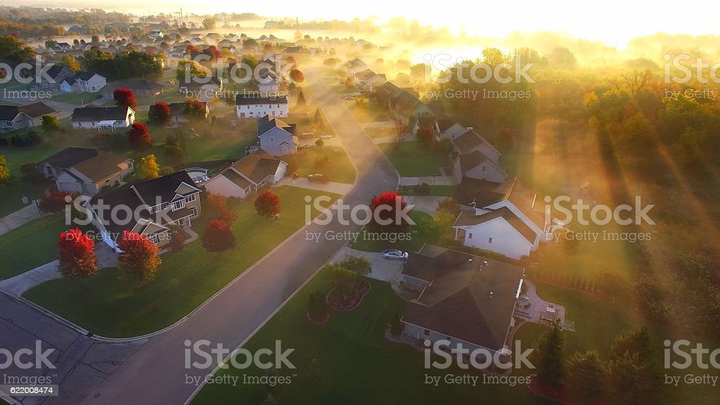 Sunrise over foggy neighborhood with shadows and sunbeams, aerial view. stock photo